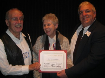 Mark Clark (left) presents the Billy Collison Award to New Ways Ministry's Sister Jeannine Gramick and Francis DeBernardo.