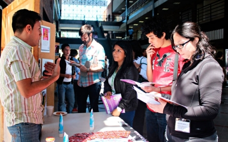 Nelson Pineda, a volunteer from Aspidh Arcoiris Trans de El Salvador, speaks with conference attendees in front of a memorial to trans women who have been murdered in El Salvador in the past decade. Aspidh Arcoiris is a Salvadoran non-profit organization that works primarily with transgender, transsexual and transvestite individuals in the areas of human rights and HIV prevention. (Courtesy of ALDES El Salvador)