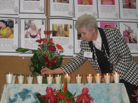 At a conference prayer service, Sister Jeannine Gramick lights candles in memory of LGBT people murdered in El Salvador.