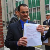 Nicholas Coppola holding a copy of the petition.