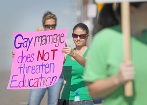 Melissa Magdaleno, an alumna, protest's the teacher's dismissal.